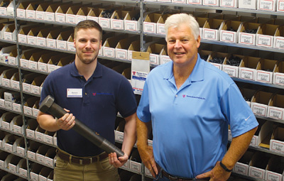 Tacoma Screw Products Wenatchee Branch Manager Aaron Bruun, left, holds a massive bolt in the store�s stock room. Next to him is Regional Outside Sales Manager Terry Lally. The store, at 1420 N. Miller St., had a soft opening in early September.  Gary B�gin/WBJ